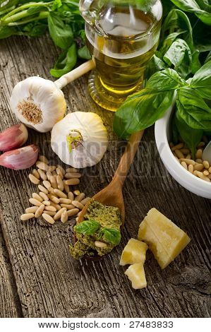 pesto sauce over spoon with ingredients