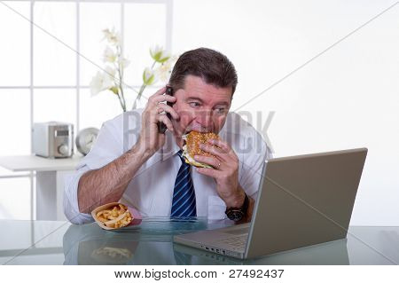 man at office with phone eat unhealthy fast food