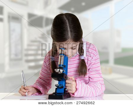 little girl looking with microscope in school laboratory