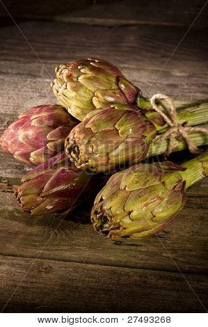 bunch of artichoke on wood background