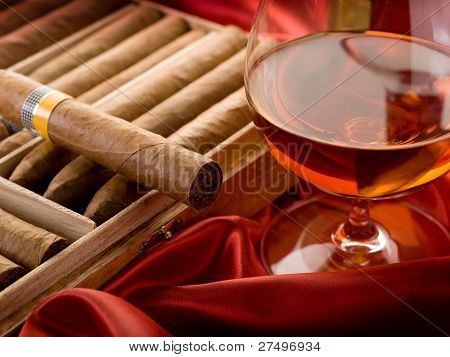 cuban cigar   and glass of liquor  over red satin