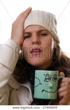 Sick A young woman is holding a cup of tea. She is sick and in pain with winter gear on. Isolated over white with space for text.