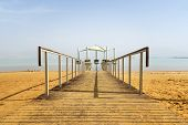 Pier On The Beach Over Dead Sea. Ein Bokek, Israel. Wooden Path On Yellow Sand Leaving In The Distan poster