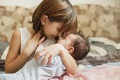 Little Sister Hugging Her Newborn Brother. Toddler Kid Meeting New Sibling. Cute Girl And New Born B poster