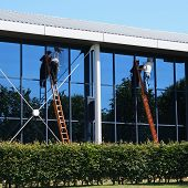 stock photo of cleaning service  - Window washers on ladders cleaning office building - JPG