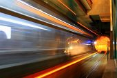 image of railcar  - Side view photo long exposure of light rail train speeding by leaving a blur of lights and gray and somewhat ghostly look to the side of subway railcar - JPG