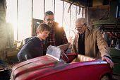 Multi Generation Family In Adiy Workshop To Repair A Pedal Car poster
