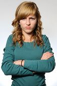 stock photo of stubborn  - Teen girl standing with her arms crossed looking frustrated - JPG