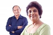 stock photo of old couple  - Portrait of a smiling elderly East Indian woman with her husband in the background - JPG