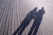 Silhouette Of A Couple Love In Casting Hand In Hand Love On A Long Shadow On Street.shadows Of Walki poster