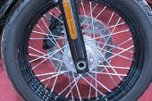 Front Wheel Motorcycle. Closeup Of Motorcycle Front Wheel And Spokes With Focus On Center Wheel Disk poster