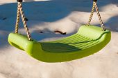 One Plastic Swing For Children With Drops Partially Illuminated From The Sunrays poster