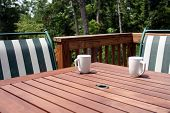stock photo of wooden table  - A table and chairs on a deck with coffee mugs on table - JPG