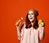 Portrait Of A Cute Casual Hipster Girl In Glasses With Orange Juice From Bottle And Apple And Orange poster