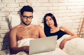 Young Couple In Bed, Man Working Laptop Bored Wife. Businessman Working On Computer In Bed While Wif poster
