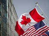 Canadian And Usa Flags In Front Of A Business Building In Toronto Ontario, Canada. Toronto Is The Bi poster