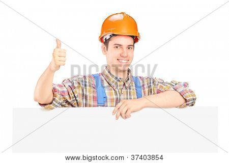 A happy male construction worker posing behind a blank panel giving thumb up