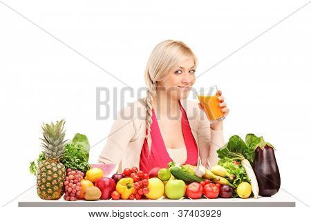 Beautiful woman drinking orange juice, on a table full of fruits and vegetables isolated on white background