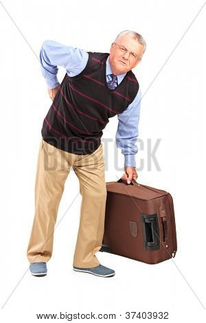 Full length portrait of a senior man lifting his luggage and suffering from a back pain isolated on white background