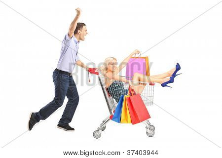 Excited person pushing a shopping cart, happy woman with bags in it, isolated on white background
