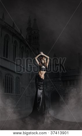 Fashion shoot of beautiful woman in a long dress over ancient background