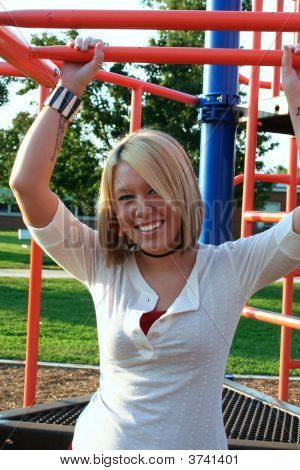 Smiling Blond On Playground Bars