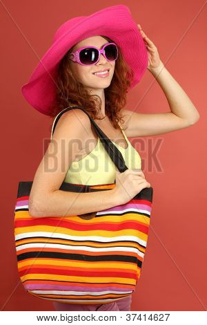 Smiling beautiful girl with beach hat, glasses and beach bag on pink background