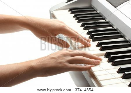 hands of woman playing synthesizer