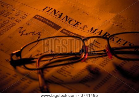 Business Section In Newspaper And Glasses