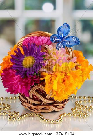Beautiful bouquet of bright flowers in small basket with paper note on white table on window background