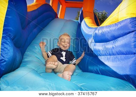 Boy sliding down an inflatable Side