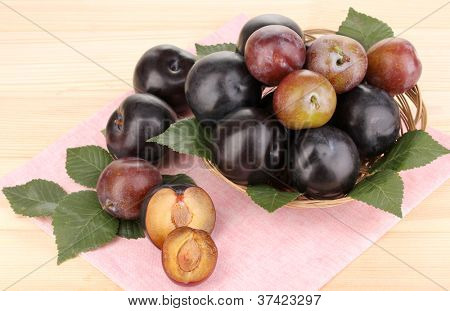 Rip plums on basket on wooden table