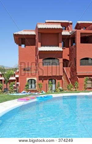Swimming Pool And Apartment Block On Spanish Vacation Urbanisation