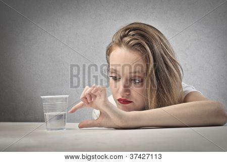 Beautiful blonde girl seeing a glass half full