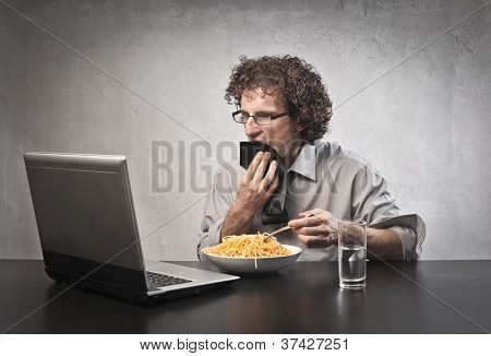 Man eating pasta while using a laptop computer