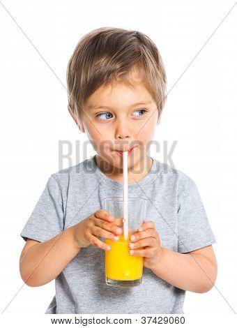 Portrait of little boy drinking orange juice