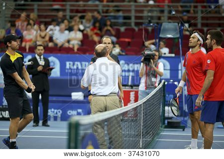 KUALA LUMPUR - SEP 30: The doubles finalists watch as the umpire tosses a coin at the start of the doubles final of the ATP Tour Malaysian Open 2012 on September 30, 2012 in Kuala Lumpur, Malaysia.