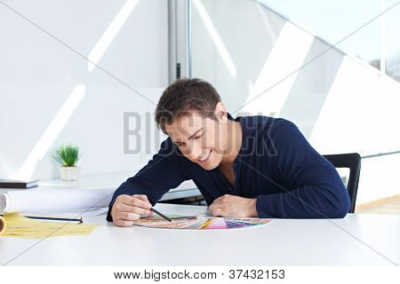 Graphic designer sitting with color fans and pencil in his office