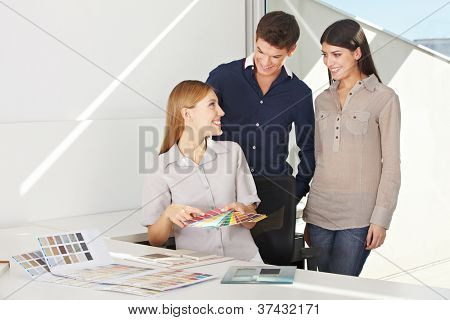 Smiling woman is consulting young couple for color advice