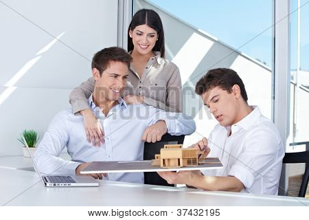 Architect showing house model to smiling couple in his office