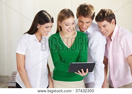 Group of happy students looking at a tablet computer
