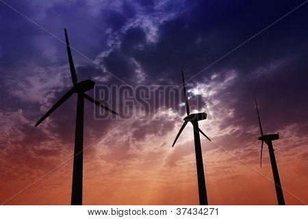 aerogenerator windmills on dramatic sunset sky green electric energy