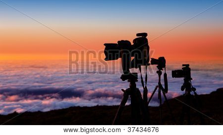camera tripods of nature photographer work in high mountain sunset over sea of clouds