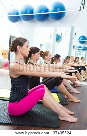 Aerobic Pilates personal trainer in a gym group class in a row