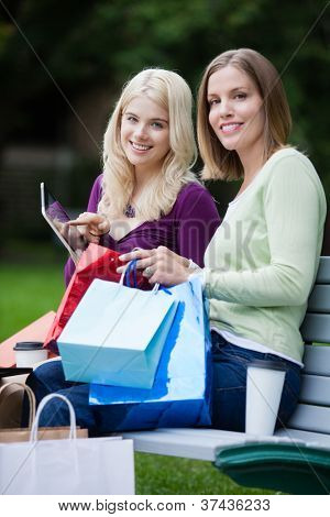 Shopping Women Using Digital Tablet on bench - shallow depth of field, critical focus on rear woman