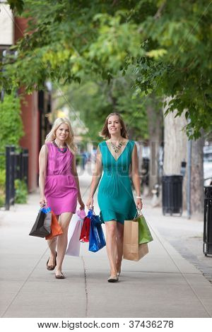 Full length of young women with shopping bags walking on sidewalk