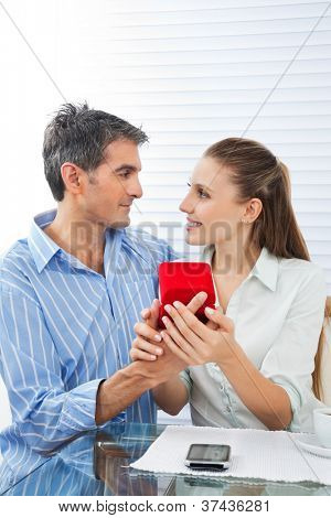 Middle aged man making proposal of marriage to beautiful woman while sitting at table