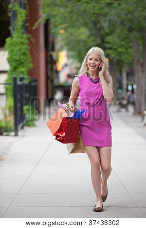 Full length of a happy young woman with shopping bags using cell phone while walking on sidewalk