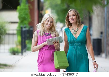 Portrait of young smiling women using digital tablet on sidewalk
