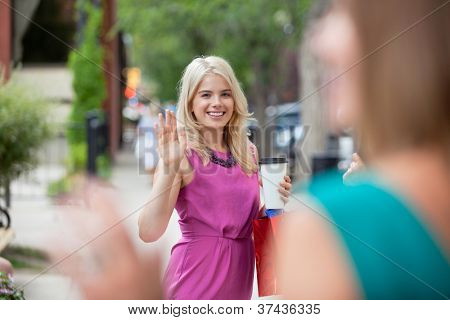 Happy young woman with disposable coffee cup waving to female friend